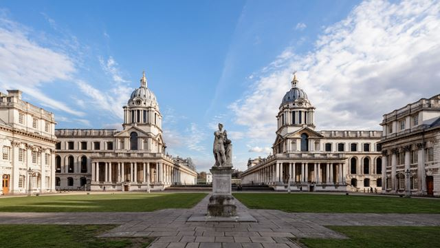 A photo of the Old Royal Naval College in Greenwich, with green grass and blue skies surrounding the building.