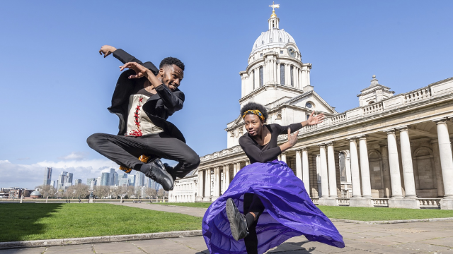 Two people dance in front of the Old Royal Naval College in Greenwich.