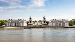 The Old Royal Naval College buildings in Greenwich sit behind shining water.
