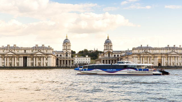 An MBNA Thames Clippers boat sails past the Old Royal Naval College in Greenwich.