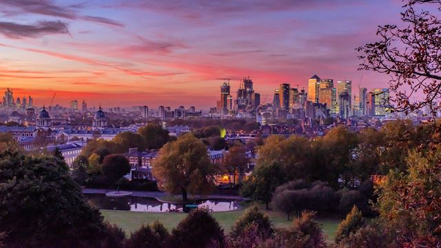 Views of a sunset over Greenwich and Canary Wharf from Greenwich Park.