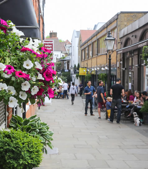 Hanging basket of flowers and people sitting outside a pub in Hampstead