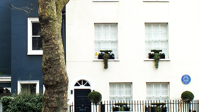 A blue plaque is on a white house with baskets of plants outside the windows.
