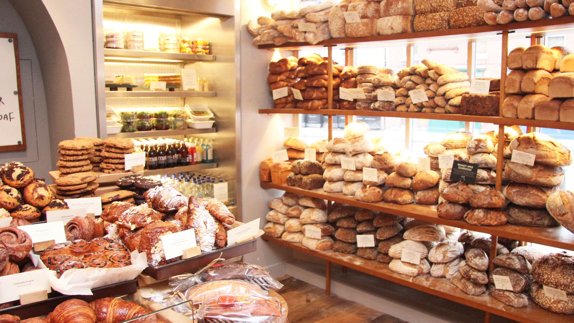 Bakery filled with freshly baked loaves on brown shelves and a counter with croissants and sweet treats.
