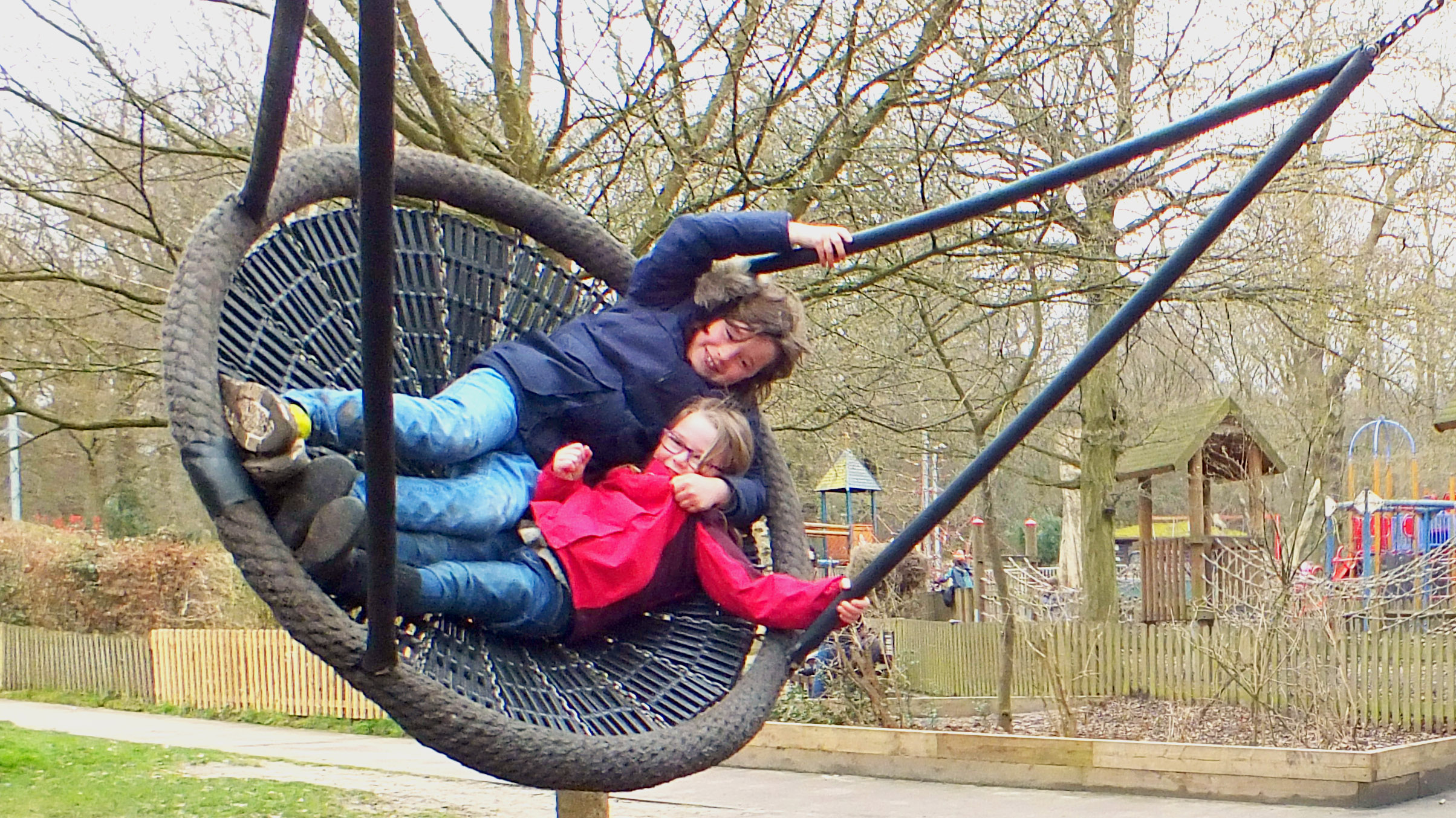 A boy and a girl play on a giant swing wrapped up in winter clothes in Highgate Playground.