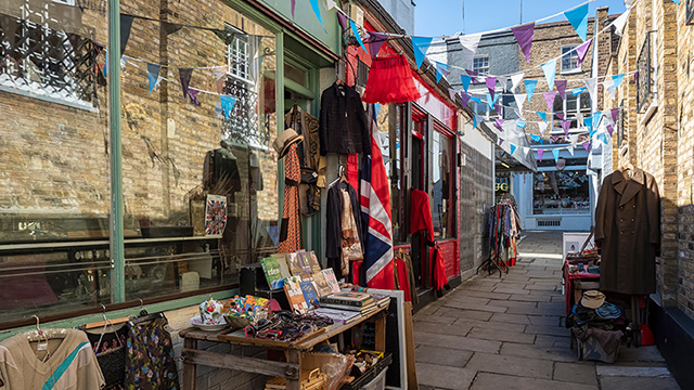 A narrow street with stalls full of knickknacks and bunting.