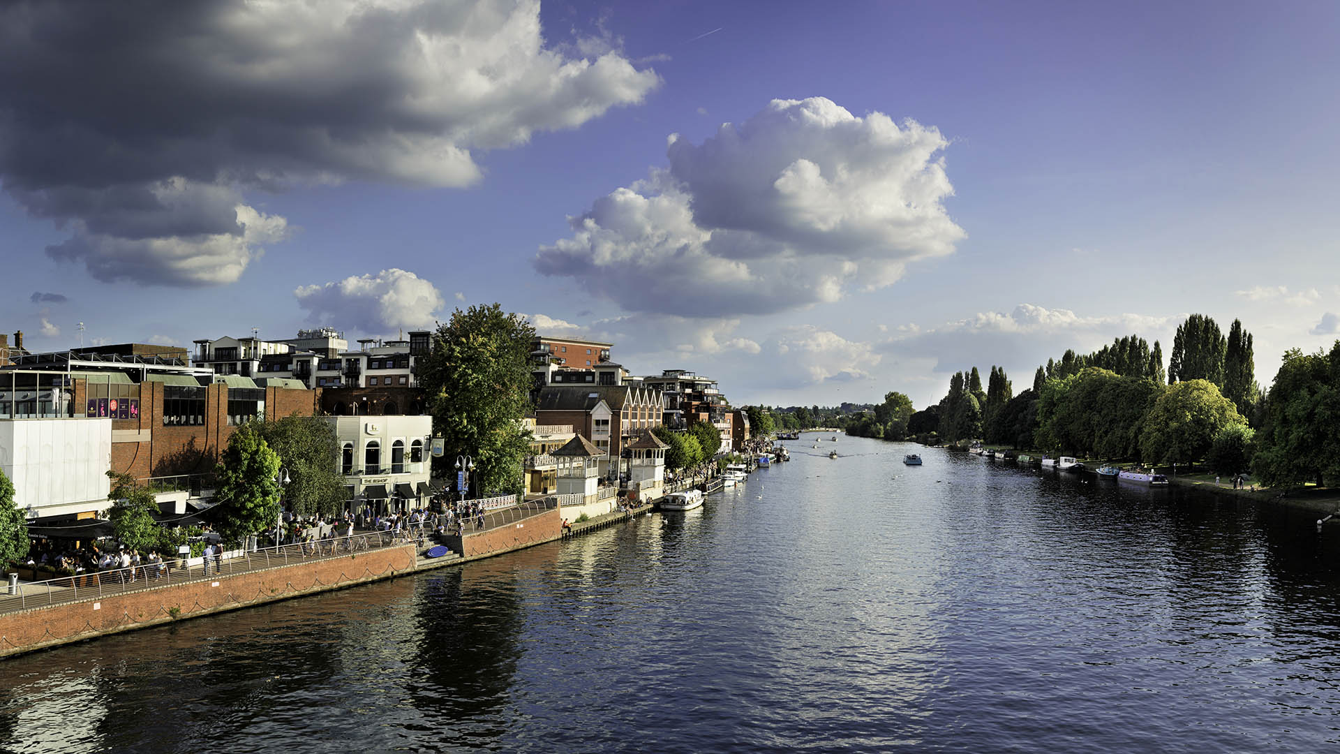 Riverside view of Kingston upon Thames with blue skies and green trees.