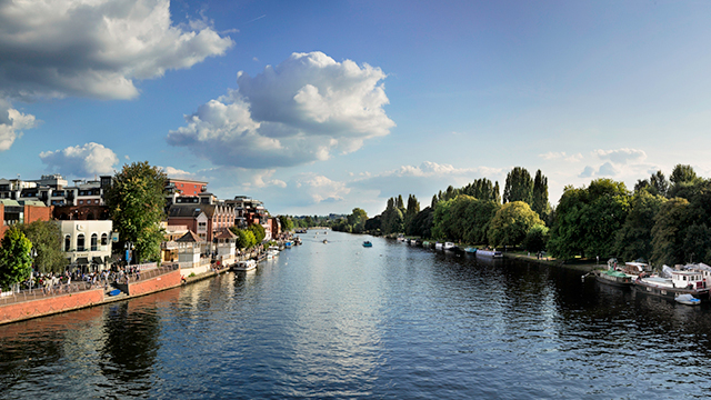 Looking at the river Thames, from a bridge, in Kingston Upon Thames on a sunny day. River boats are moored on the right bank, surrounded by trees; while there are buildings and a walkway on the left bank.