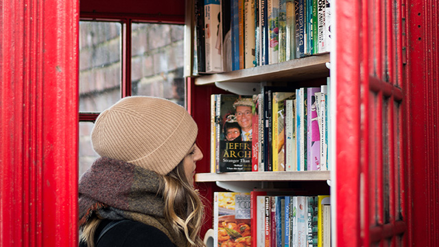 A lady, wearing a beanie hat, studies the books within the phone box library.