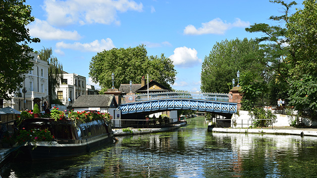 Looking down the canal at Little Venice with a bridge going over the canal and a canal boat on the left, on a sunny day.