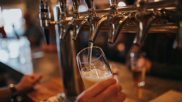 A pint is held by a hand as it is being poured.