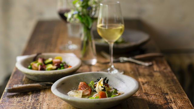 A close-up of two beautifully-dressed plates and a glass of white wine on a rustic wooden table.