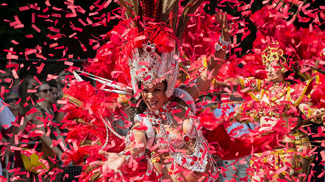 A carnival queen dressed in a white costume with red feathers, surrounded by red ticker tape dancing at the Notting Hill carnival