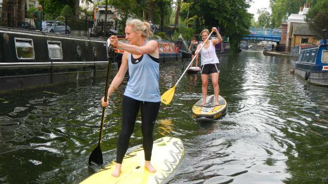 Girls paddle boarding along Paddington canal