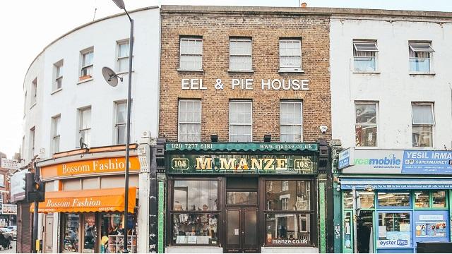 Exterior of M Manze shop on Peckham High Street, with eel & pie house written on brick wall overhead