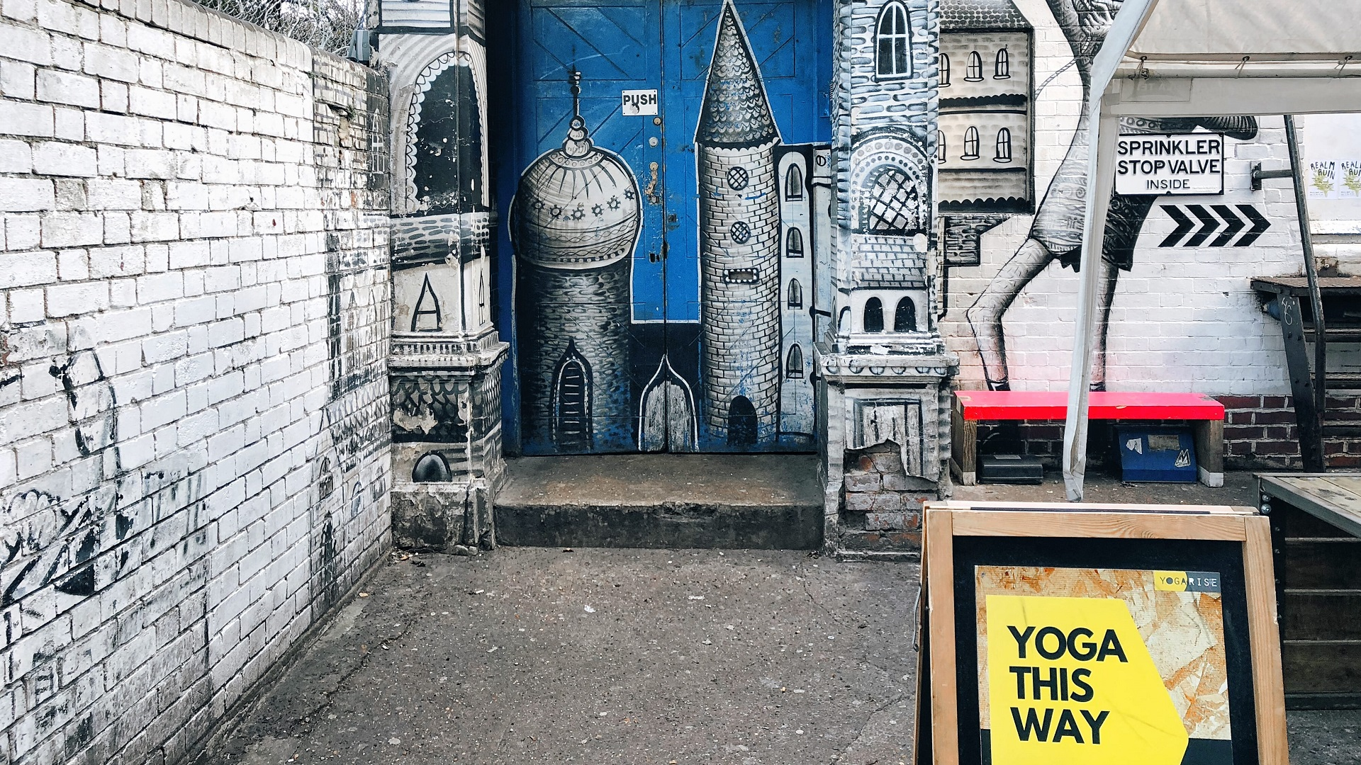 Street art of a castle on a blue door way behind a yellow sign reading Yoga this way