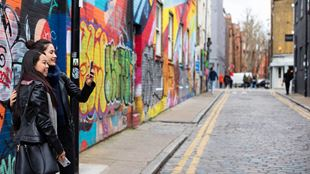 Two women take a selfie in front of colourful street art in a Shoreditch street.