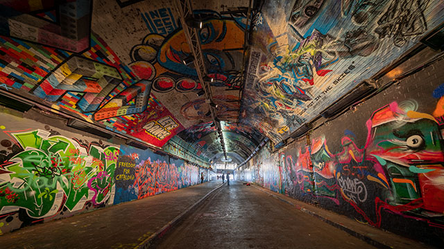 Looking along an empty Leake Street Tunnel, which is decorated with colourful street art on the walls and ceiling, with daylight visible at the end of the tunnel.
