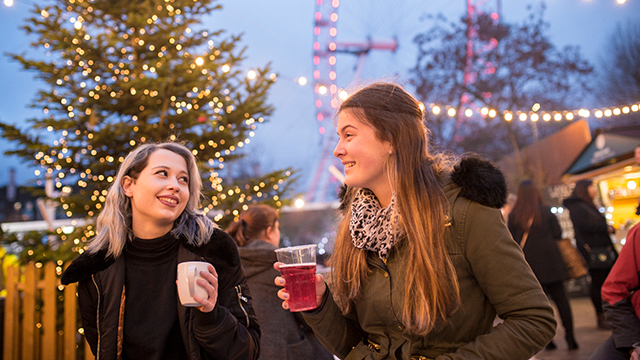 Two women, wearing winter clothes, smile at each other while holding glasses of drink, while fairy lights and the London Eye are illuminated in the background.