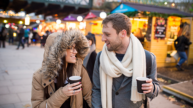 A woman and man walk along the South Bank, wearing wintry clothing and holding hot drinks, with lit market stalls in the background.