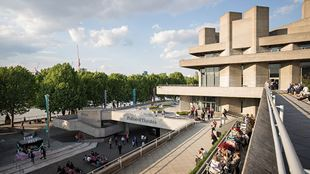 A view from the balcony of the Southbank Centre, with the brutalist-style National Theatre on the right and the riverside walkway on the left.