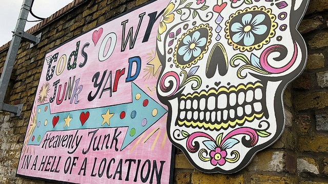 Pink sign on a brick wall reads Gods Own Junk Yard, Heavenly Junk in a Hell of a Location
