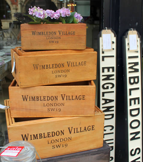 Wooden boxes with Wimbledon Village written on, filled with flowers