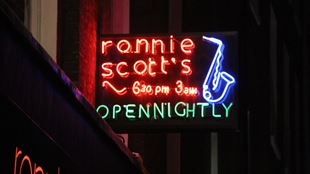 The red neon sign of Ronnie Scott's Jazz Club in Soho lit up during night time.