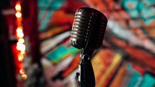 A vintage microphone with a blurred background of fairy lights and graffitis.