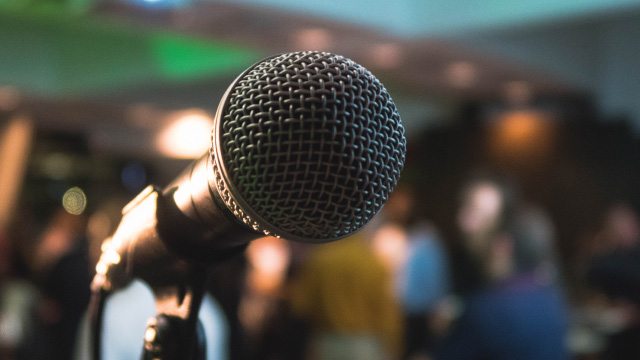 A karaoke microphone on stage in front of an audience