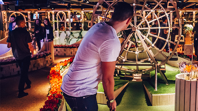 A man lines up a shot at one of Swingers' crazy golf holes, which includes a small wooden version of a big wheel.