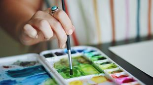 A woman dips a painting brush in a pallet of watercolour paints and mixes colours.