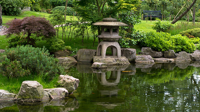A Japanese-style sculpture reflects in the water of a pond in Kyoto Garden, with acers surrounding the pond.