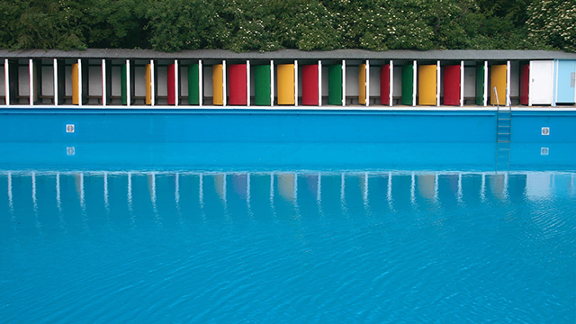 The bright blue lido in the foreground and colourful red, green and yellow doors of the changing rooms in the background.