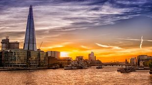London skyline including the prominent building of The Shard, with an orange sunset in the background.