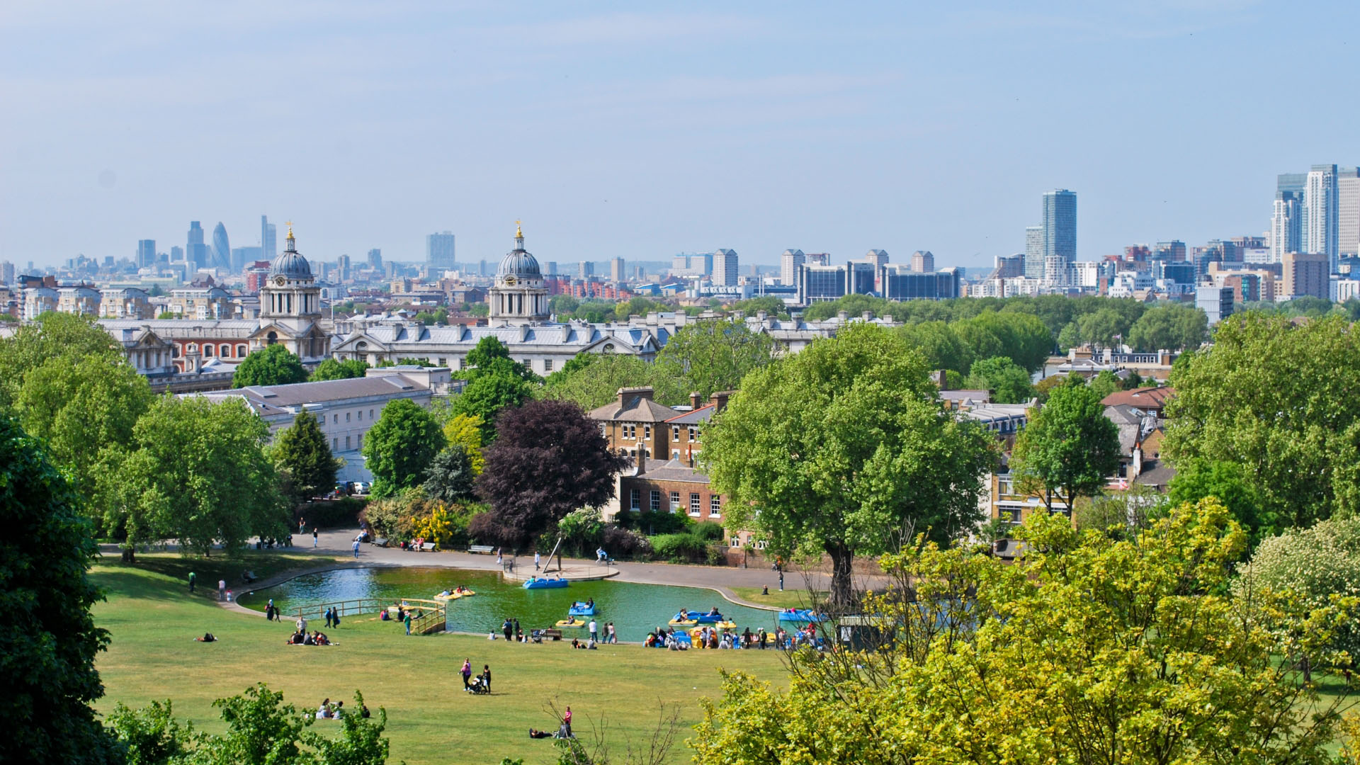 People sit on green lawns in Greenwich Park in front of a view of the London skyline.