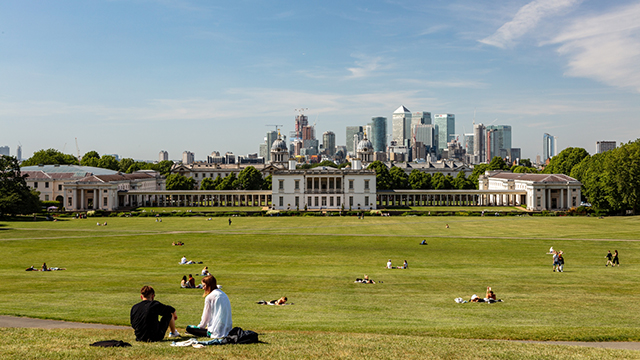 Groups of people sit on the hill of Greenwich Park overlooking the Old Royal Naval College and the London skyline.