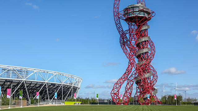 The red, twisting structure of the ArcelorMittal Orbit on the right, and London Stadium on the left, on a bright day.