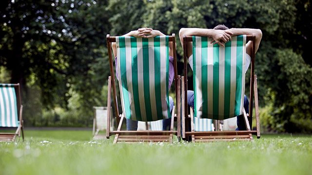 Two people relax on green and white striped deckchairs, facing away from the camera, on the grass at St James's Park.