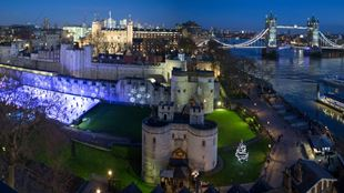 Aerial shot of Tower of London at night, with an ice rink lit up on the left and Tower Bridge lit up on the right