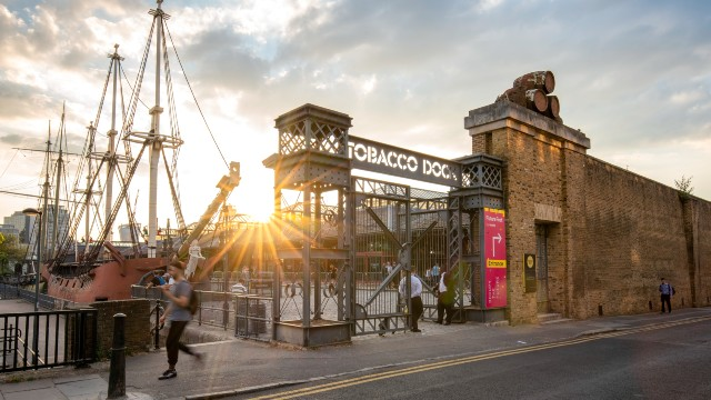 Tobacco Dock building at dusk with ships in the background.