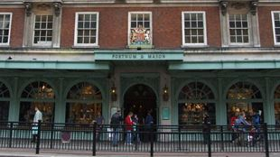 The pale green shop front of Fortnum & Mason with its crest and people walking past along Piccadilly.