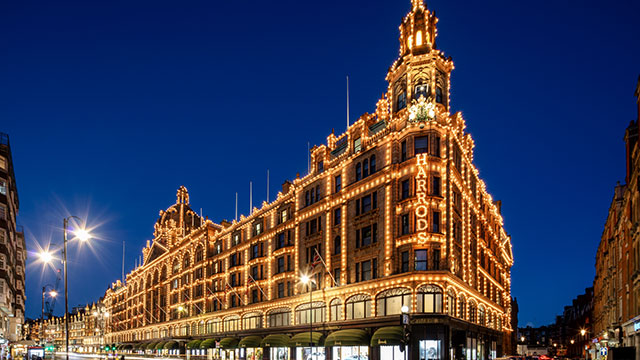 "Harrods department store lit up at night in its trails of yellow lights and illuminated ""Harrods"" sign, against a dark blue sky and illuminated street lights."