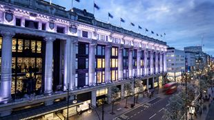 A panoramic view from high of the facade of Selfridges, lit up in purpley-white lights, with Oxford Street below.