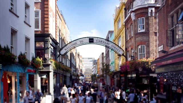 People walking thorugh Carnaby Street, with blue skies above.