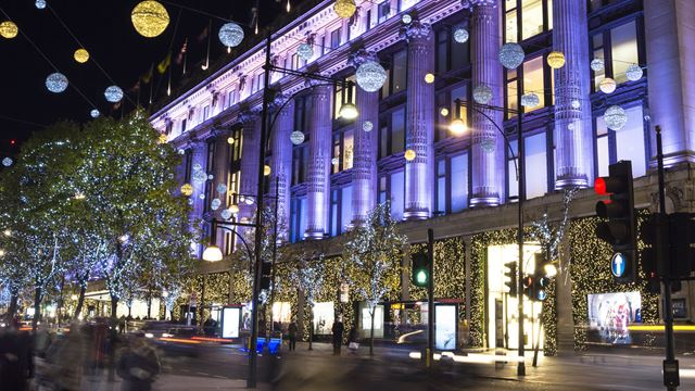 Shoppers and cars pass Selfridges, covered in twinkling lights for the festive season.