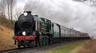 A black and green steam train billows out steam as it moves on tracks towards the camera, with grass verges to the side.