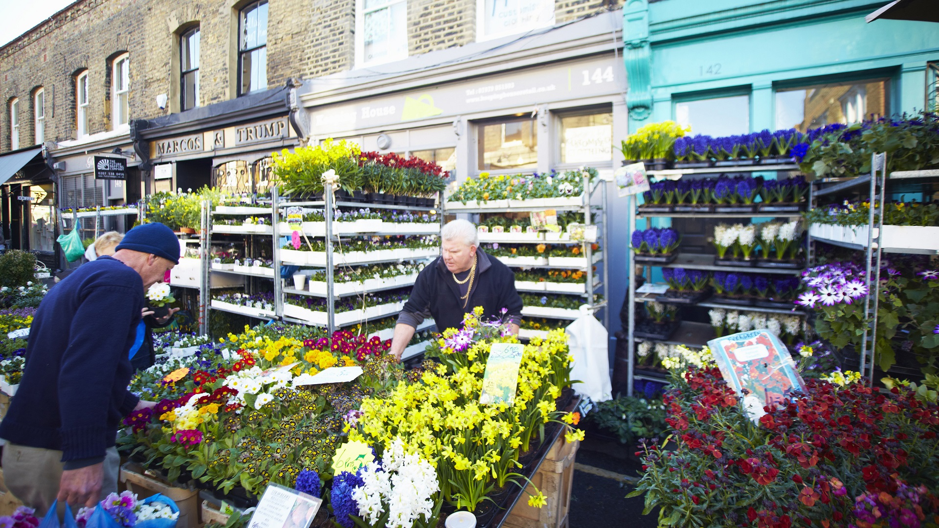 Market seller surrounded by daffodils and other plants at Columbia Road Flower Market