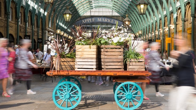 A cart topped with green plants in the middle of Covent Garden's Apple Market.