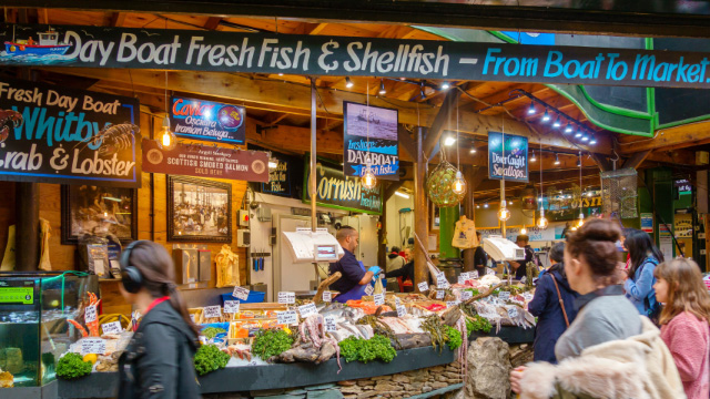 People shop for fresh fish at Borough Market in London.